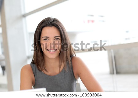 Portrait of smiling student girl working on laptop - stock photo
