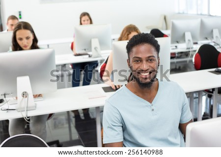 Portrait of smiling students in computer class - stock photo