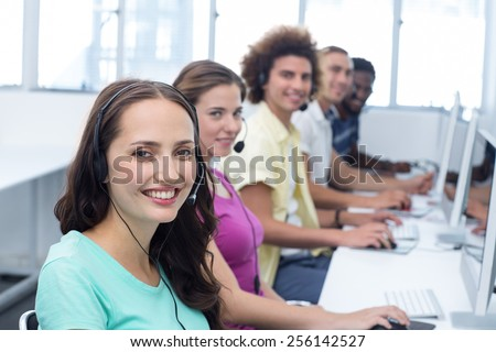 Portrait of smiling students using headsets in computer class