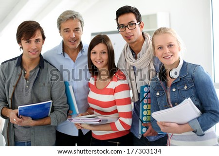 Portrait of smiling students with teacher - stock photo
