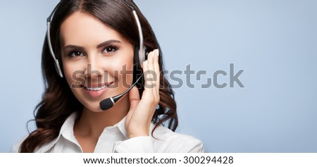 Portrait of smiling support female phone operator in headset, against grey background. Consulting and assistance service call center. - stock photo