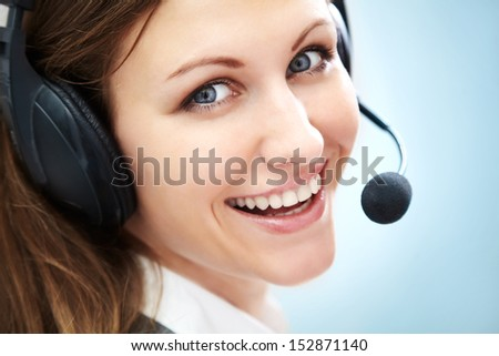 Portrait of smiling support phone operator in headset, over blue background - stock photo