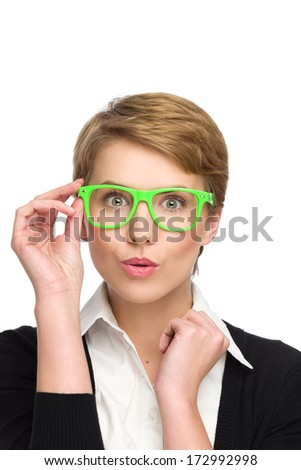 Portrait of smiling surprised young woman in green glasses. Head and shoulders studio shot isolated on white.