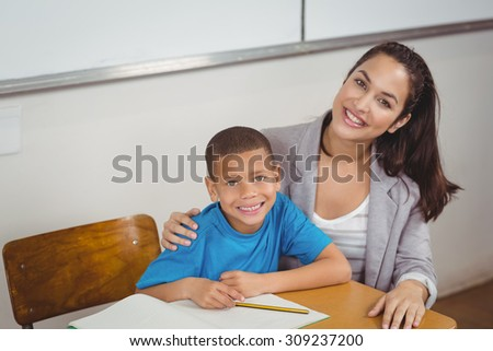 Portrait of smiling teacher and her pupil sitting at desk in a classroom - stock photo