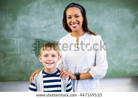 Portrait of smiling teacher and schoolboy standing in classroom at school - stock photo