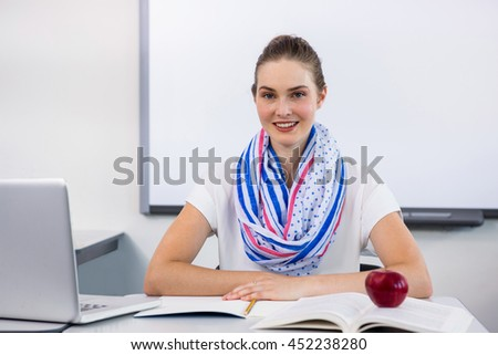 Portrait of smiling teacher sitting at desk with laptop and books in classroom
