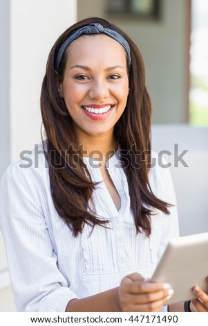 Portrait of smiling teacher using digital tablet in classroom at school