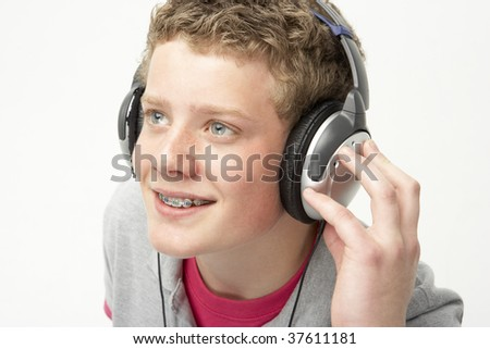 Portrait of Smiling Teenage Boy Listening to Music - stock photo