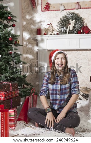 Portrait of smiling teenager girl in santa hat near christmas present box and laugh. She is sitting on artificial snow - stock photo