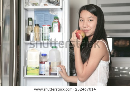 Portrait of smiling teenager girl with apple in kitchen - stock photo