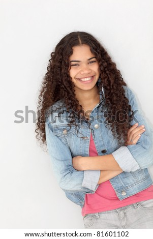 Portrait of smiling teenager leaning on wall - stock photo