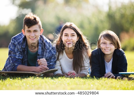 Portrait of smiling teenagers on countryside field in autumn day. Focus on boy