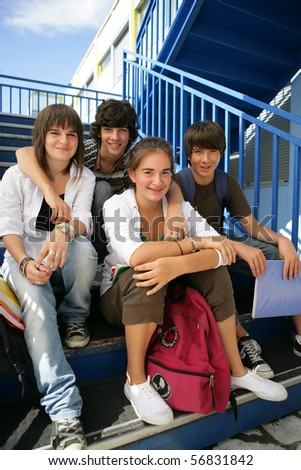 Portrait of smiling teenagers sitting on the steps of stairs - stock photo