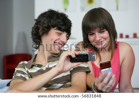 Portrait of smiling teenagers with mobile phones - stock photo