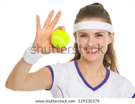 Portrait of smiling tennis player showing tennis ball