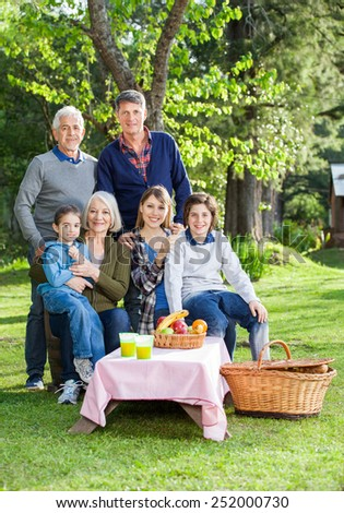 Portrait of smiling three generation family enjoying picnic in park - stock photo