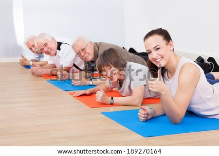 Portrait of smiling trainer and senior customers performing yoga on floor at gym