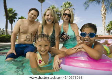 Portrait of smiling two girls with parents and grandmother in the swimming pool - stock photo