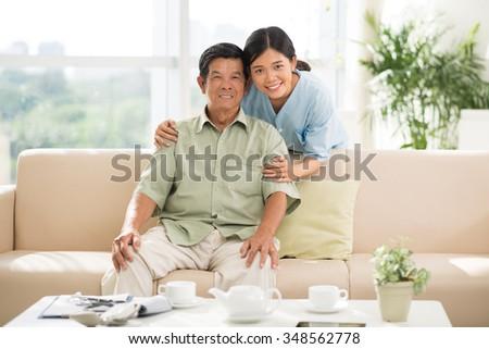 Portrait of smiling Vietnamese doctor hugging senior man - stock photo