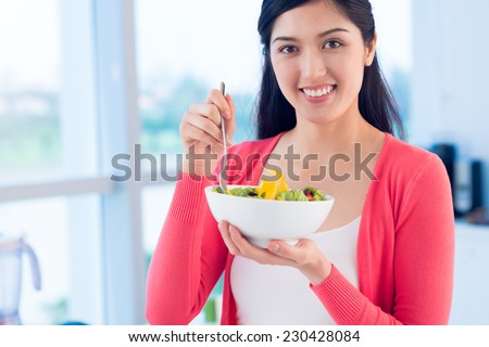 Portrait of smiling Vietnamese woman eating vegetable salad - stock photo