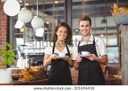 Portrait of smiling waiter and waitress holding cup of coffee at coffee shop - stock photo