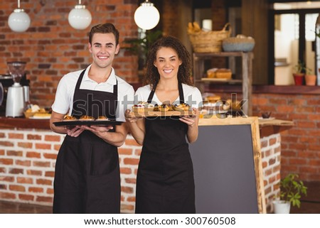 Portrait of smiling waiter and waitress holding tray with muffins at coffee shop