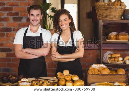 Portrait of smiling waiter and waitress with arms crossed at coffee shop - stock photo