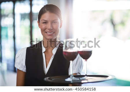 Portrait of smiling waitress holding a tray with glasses of red wine