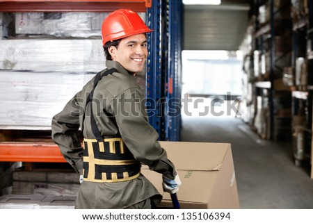 Portrait of smiling warehouse worker pushing handtruck with cardboard boxes - stock photo
