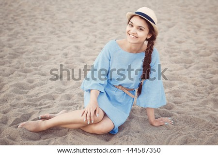 Portrait of smiling white Caucasian brunette woman with tanned skin in blue dress and straw hat sitting on sand beach shore, sunset on summer day, lifestyle concept