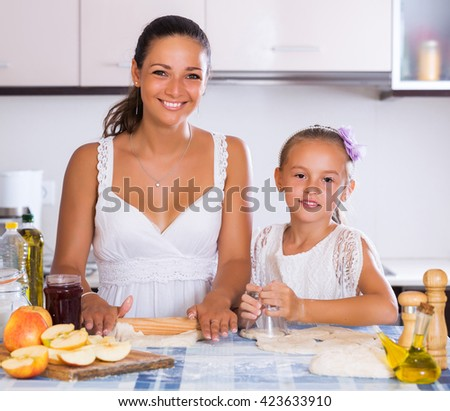 Portrait of smiling woman and child cooking apple strudel