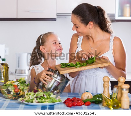 Portrait of smiling woman and little girl cooking vegetables