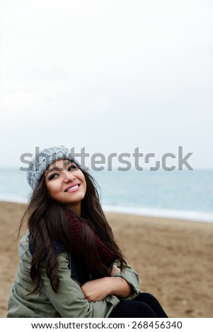 Portrait of smiling woman at leisure time outdoors with copy space area, cold autumn day, attractive happy girl on promenade on the beach with beautiful sea on background - stock photo