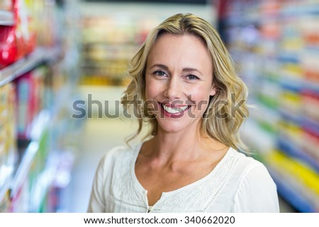 Portrait of smiling woman at the supermarket - stock photo