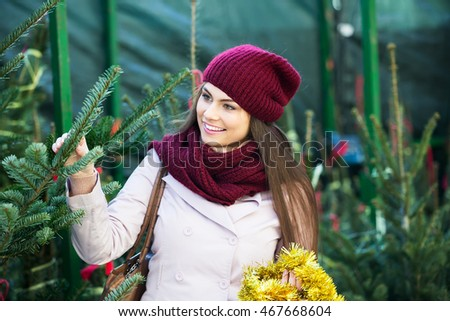 Portrait of smiling woman  choosing New Year's tree in fair
