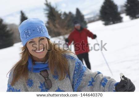 Portrait of smiling woman cross country skiing with blurred man in the background - stock photo