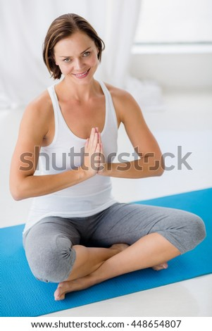 Portrait of smiling woman doing yoga at fitness studio