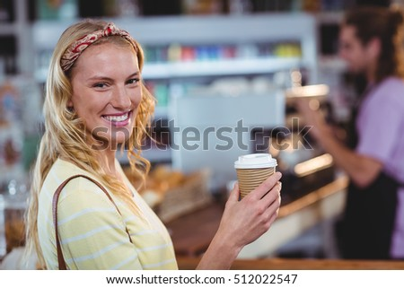 Portrait of smiling woman holding cup of coffee in café
