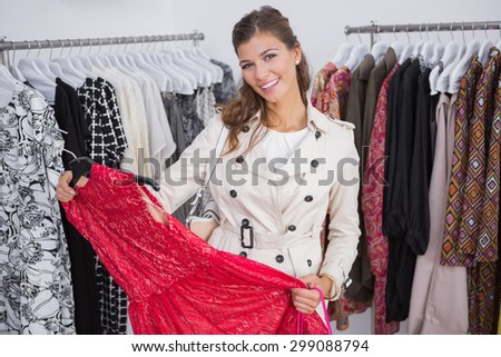 Portrait of smiling woman holding red dress and looking at camera at a boutique - stock photo
