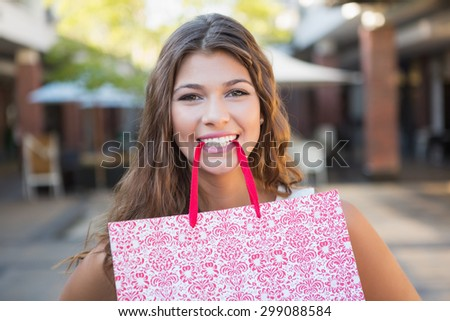 Portrait of smiling woman holding shopping bag in her mouth at the shopping mall