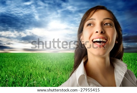 portrait of smiling woman in a grass field - stock photo