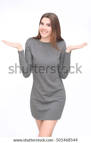 Portrait of smiling woman in grey dress with palms up