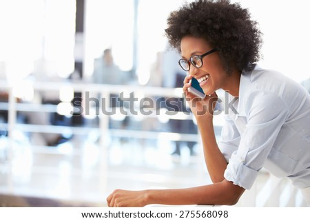 Portrait of smiling woman in office talking on phone - stock photo