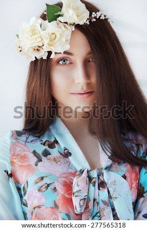 Portrait of smiling woman in spring dress and floral crown near the wall - stock photo
