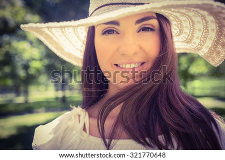 Portrait of smiling woman in sun hat while standing in park - stock photo