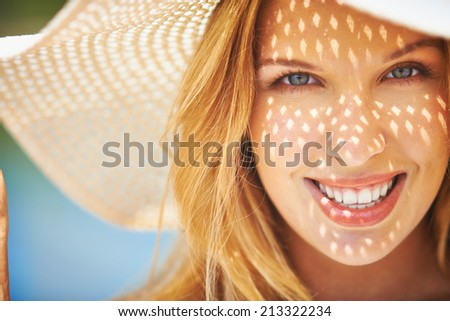 Portrait of smiling woman in sunhat looking at camera - stock photo