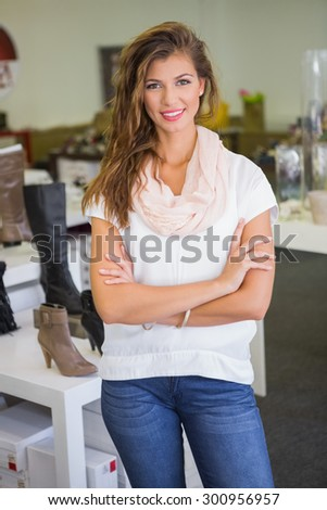 Portrait of smiling woman looking at camera with arms crossed at a shoe shop
