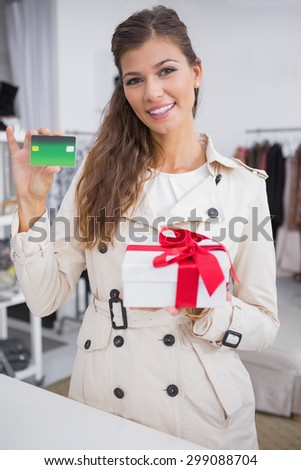 Portrait of smiling woman paying a gift by credit card at a boutique - stock photo