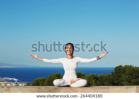 Portrait of smiling woman practicing yoga by raising her hands feeling so good and happy, young woman seeking enlightenment through meditation, relaxed girl performing and enjoy yoga routine, filter - stock photo