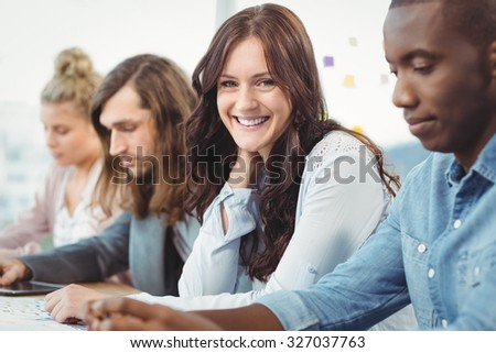 Portrait of smiling woman sitting at desk with coworkers in office